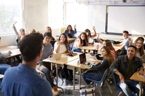 Rear View Of Male High School Teacher Standing At Front Of Class Teaching Lesson